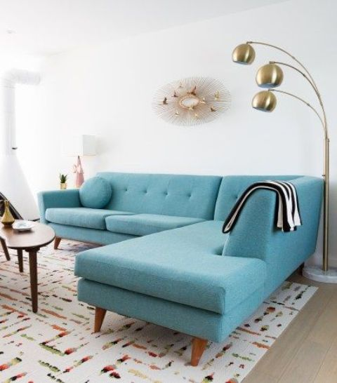 a large turquoise sectional sofa takes a half of this tiny space but it doesn't look small