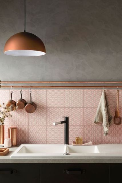 a pink tile backsplash is accented with copper railings and some kitchen stuff on them
