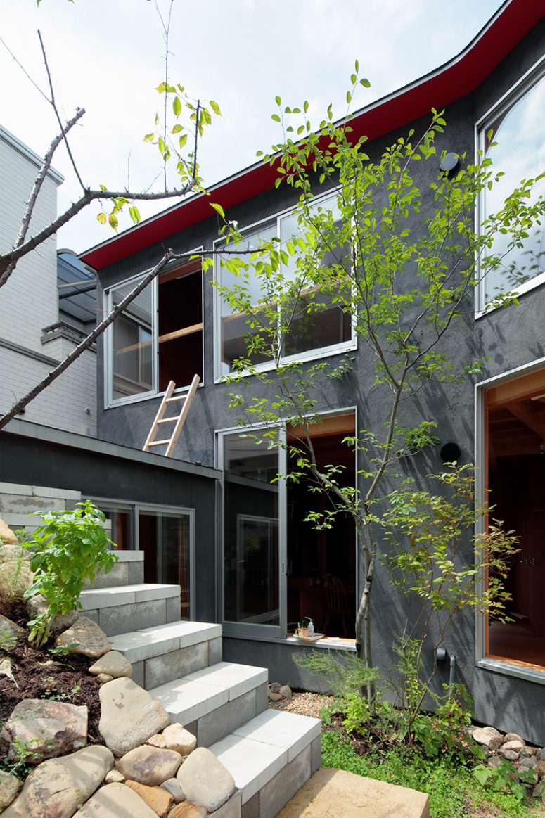 Greenery and rocks look very interesting in front of a modern dark grey home