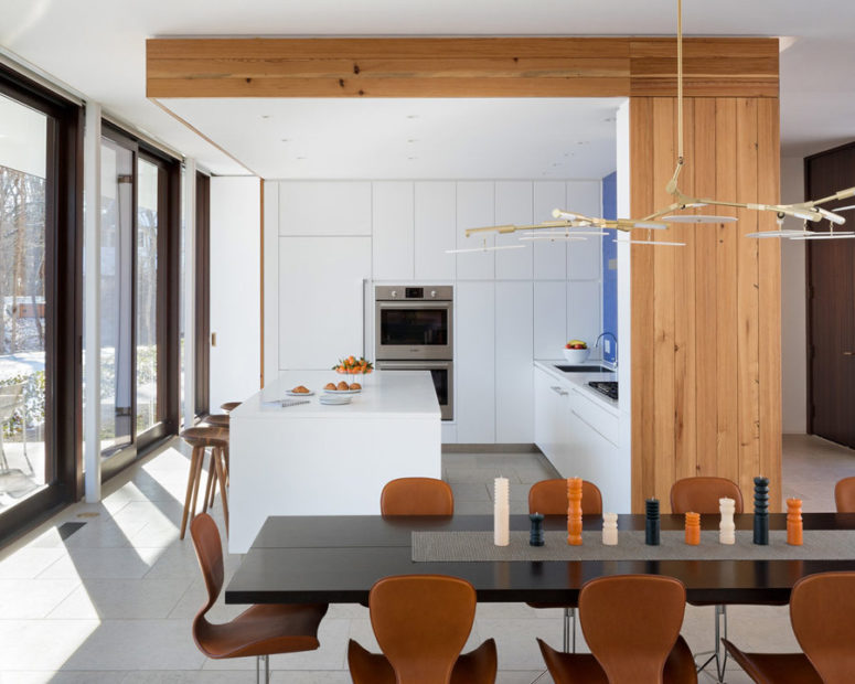 The kitchen block features its own ceiling with built-in lights and wood cladding the side and ceiling