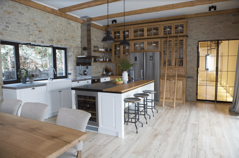 The kitchen is done with white and light colored wooden cabinets, with stainless steel appliances