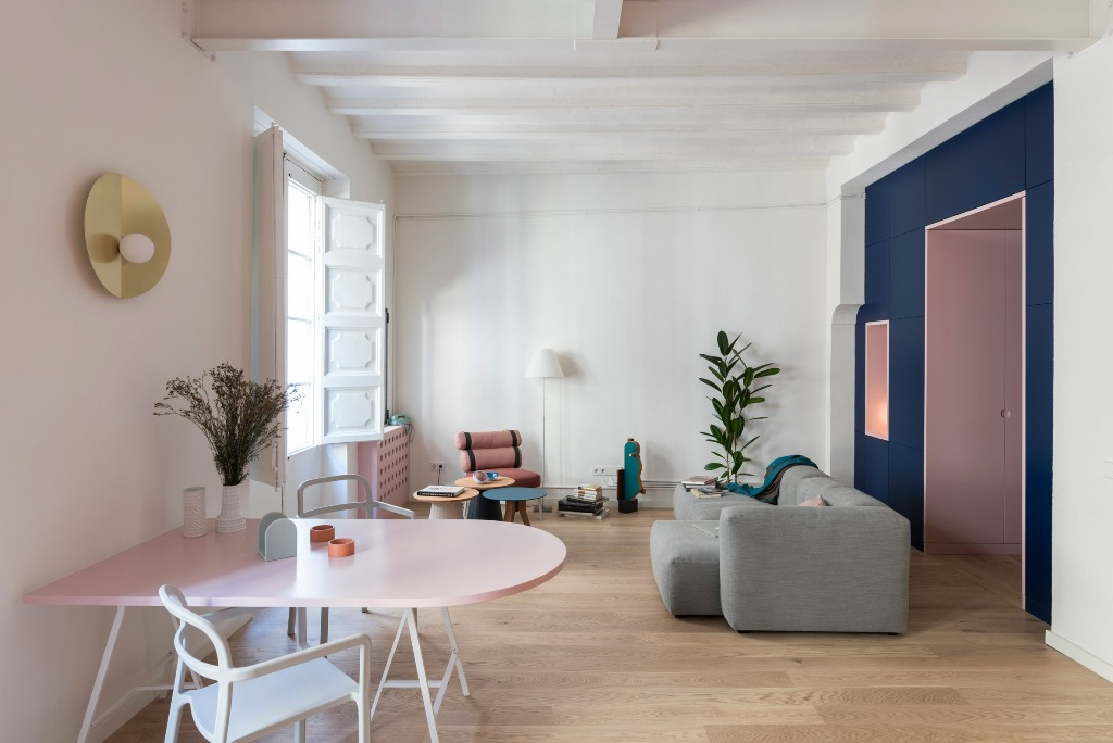 The living room is dominated by a large grey sofa and a couple of colorful furniture units