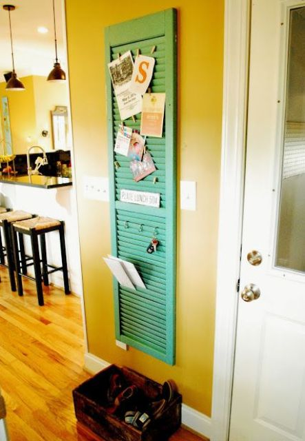 a green painted shutter works as a pinboard and a key holder in the entryway