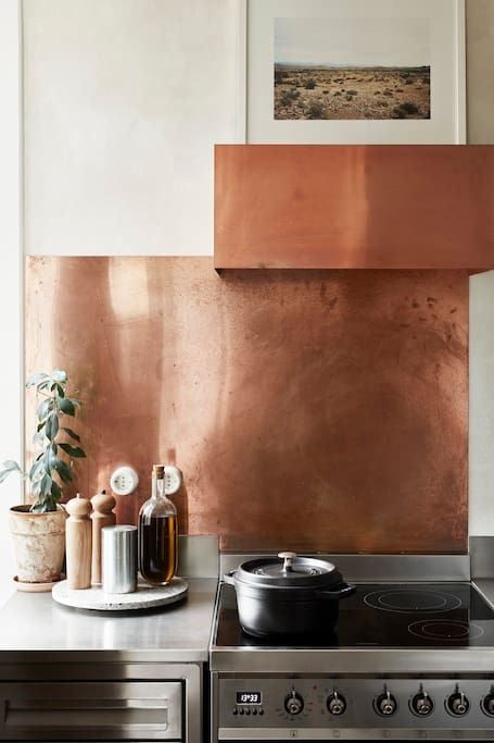 a polished copper sheet backsplash and a matching hood to make the kitchen bolder and cooler