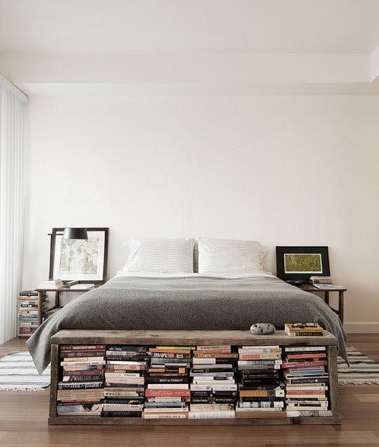 an industrial bedroom with a storage bench and rugs on both sides of the bed