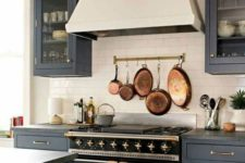 03 make a neutral backsplash more eye-catchy with a rail and vintage pots and frying pans