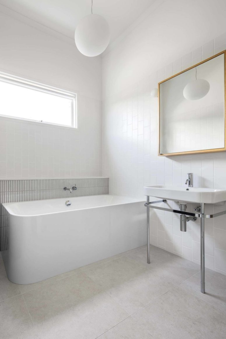 The bathroom is white and sleek, there's a free-standing bathtub, white tiles and a modern mirror