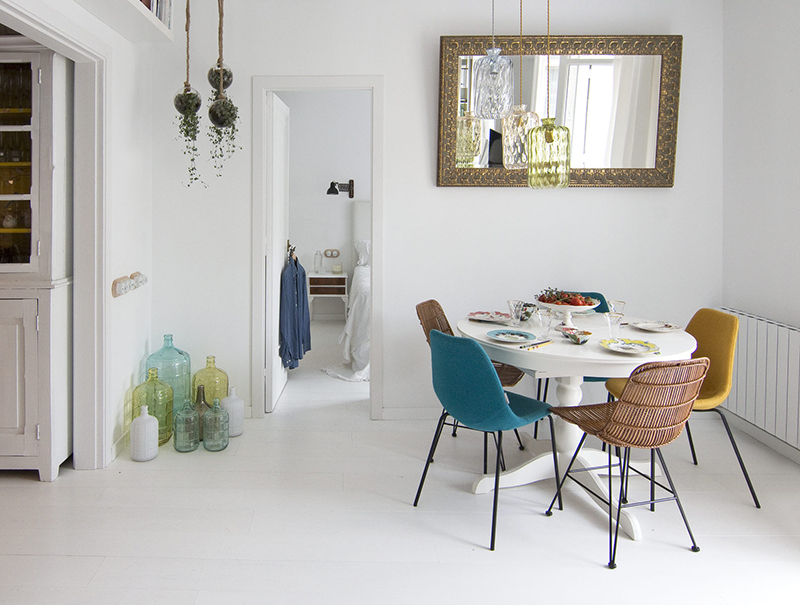 The dining space is done with mismatching chairs, a round table and a vintage mirror
