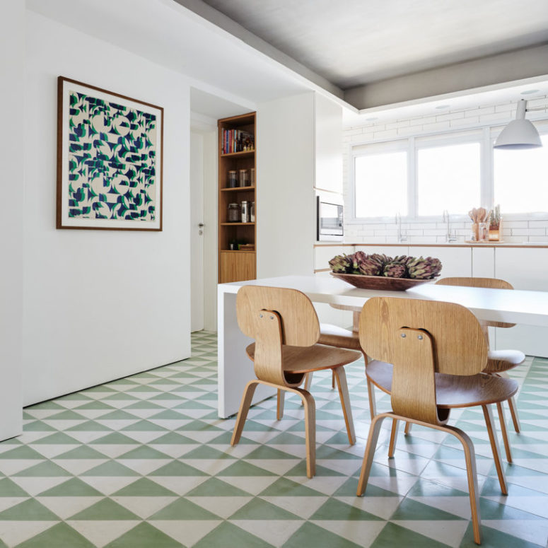 The floors are clad with geometric tiles in green and white, and there's a matching artwork
