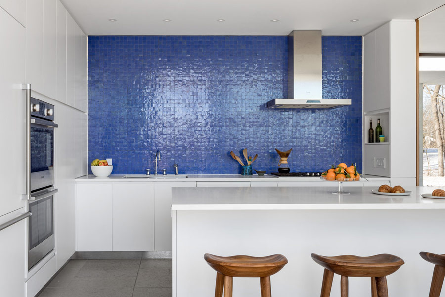 The kitchen is done with white cabinets and a kitchen island, and the backsplash wall is clad with purple tiles