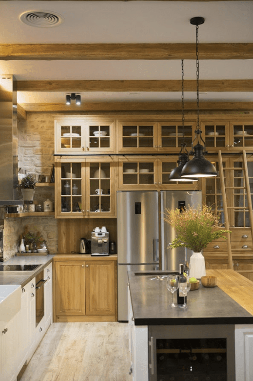The kitchen island includes a wine cooler, and the lamps are industrial ones