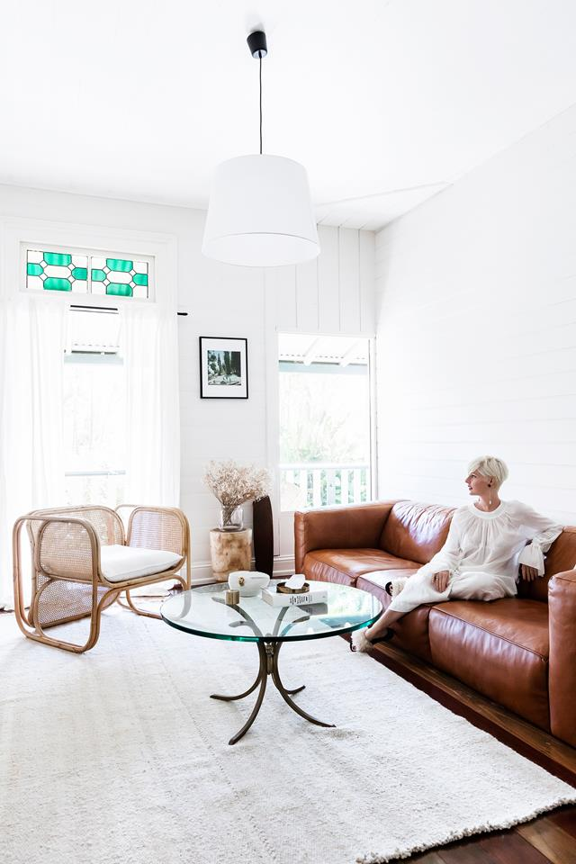 The living room is done with mid-century modern furniture, a brown leather sofa and some mosaics that adds to the decor
