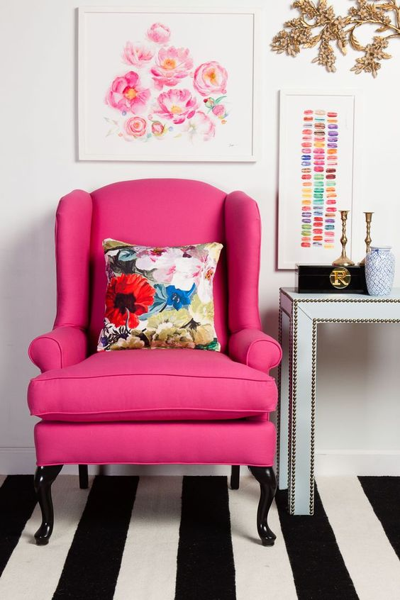 a boring classic wingback is given a fresh look with hot pink upholstery to match a girlish space