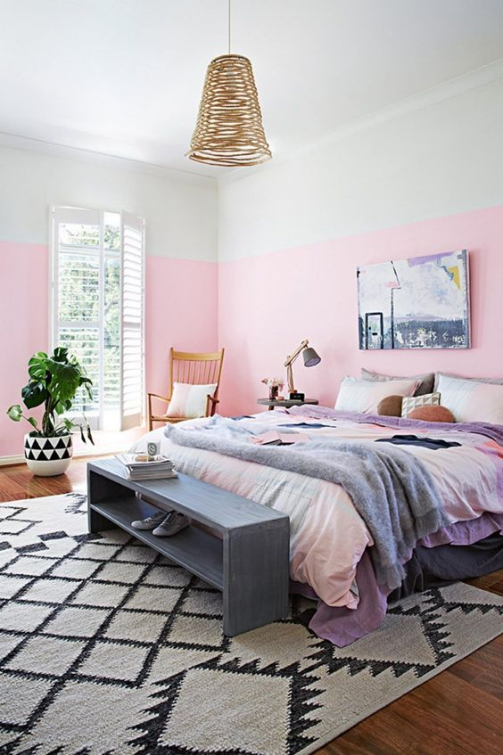 a colorful bedroom with watercolor bedding, a wicker pendant lamp and a vintage storage bench