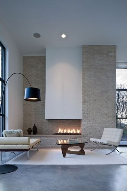 a refined asymmetric fireplace with a neutral brick wall and a sleek white hood is a focal point here