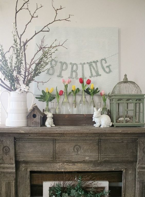 a rustic console with greenery, colorful tulips in clear vases and a spring banner