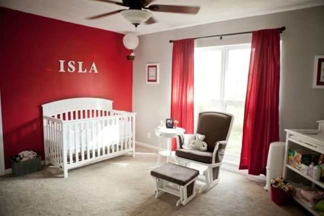 red curtains and a red statement wall is a great choice for a nursery
