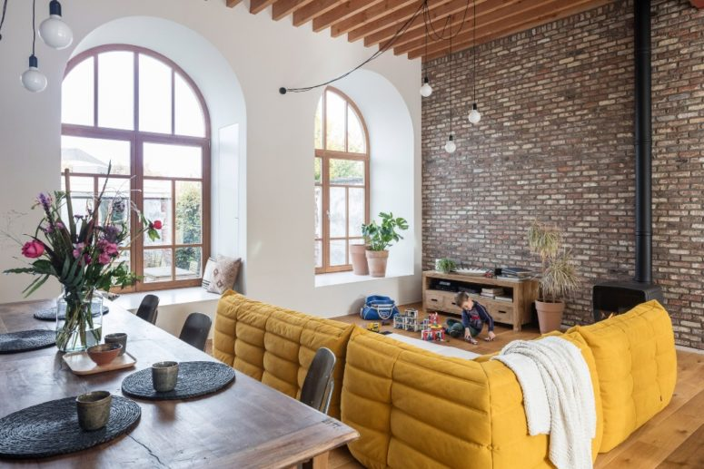 The dining space is created with an industrial dining set, metal chairs and a wooden table, the living room is defined with a bold yellow L-shaped sofa