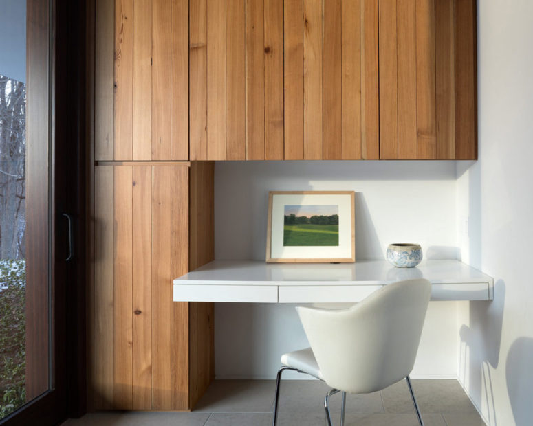 The home office nook is done with wood clad cabinets and a floating desk with a comfy chair
