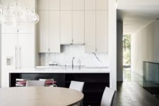05 The kitchen and dining space are united, there are upper cabinets of different height, a marble backsplash and modern leather chairs