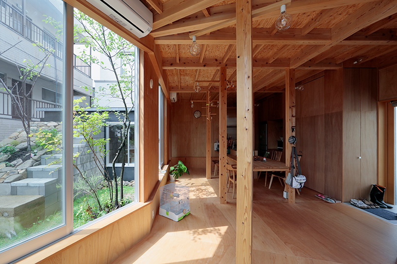 The lower floor is clad with wood and here you can see a dining space and a kitchen