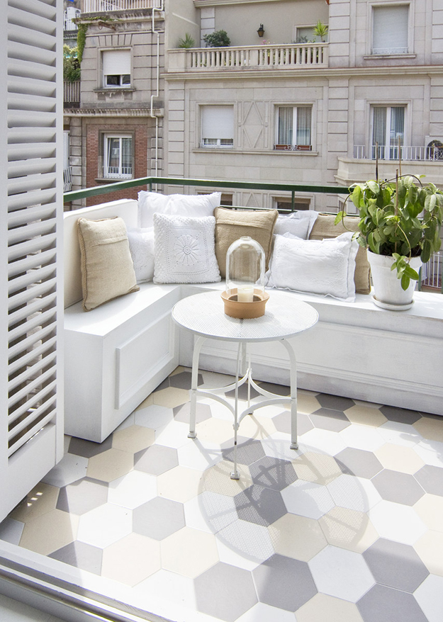 There's a nice and comfy terrace with a geometric tile floor and a comfy nook for breakfast