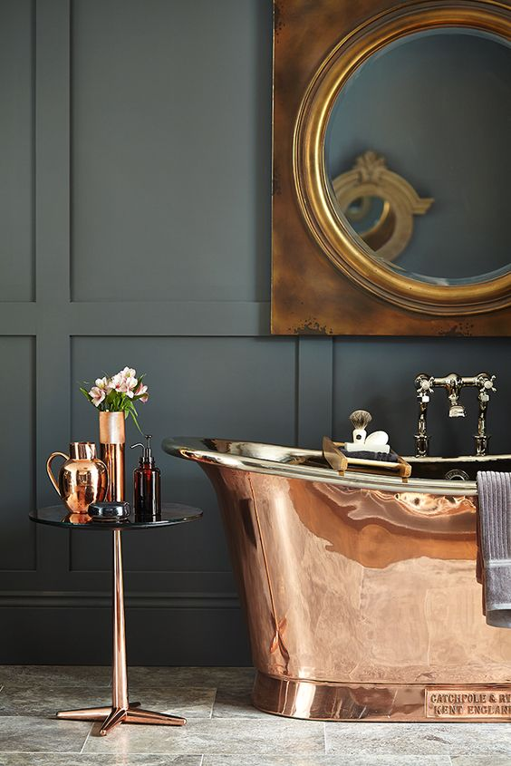 a brass free-standing bathtub, a matching table and vases for a refined and catchy look