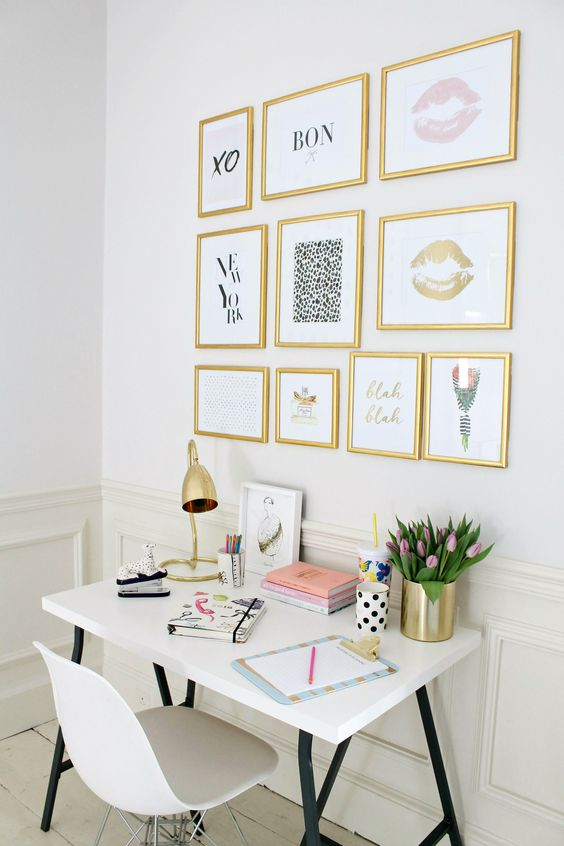 a girlish workspace with a gallery wall with gold frames and various girlish art
