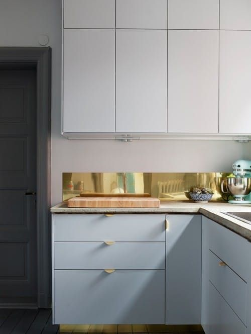 a narrow polished gold kitchen backsplash to add interesting to a plain white kitchen