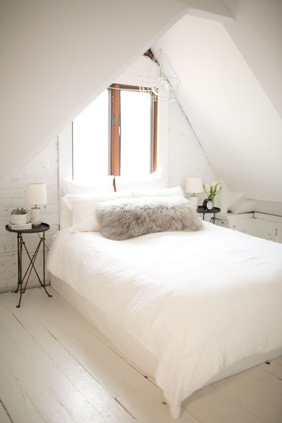 a neutral attic space with a bed in the center and little nightstands on both sides