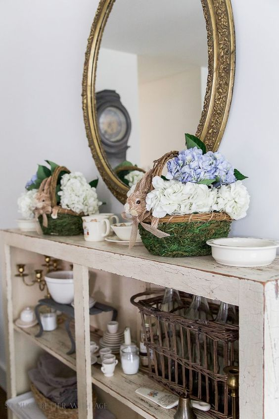 a shabby chic console with moss baskets with bunny faces and hydrangeas