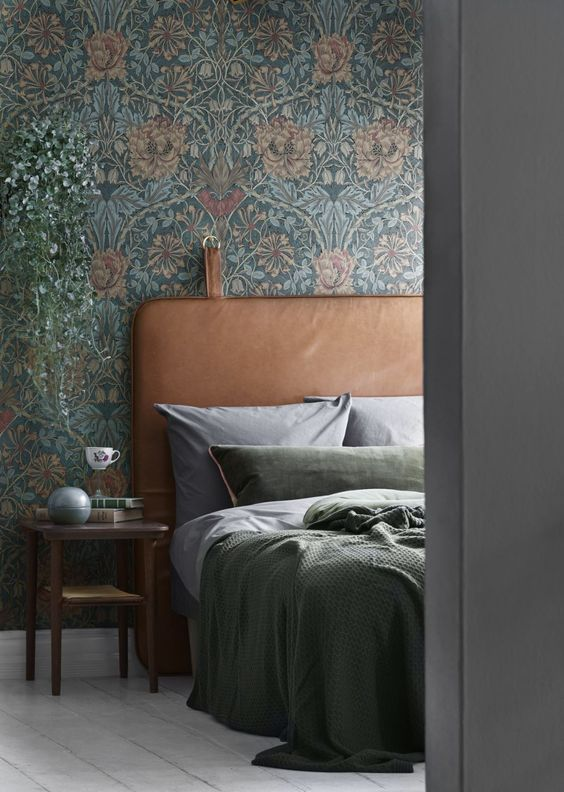 vintage-inspired floral print wallpaper and a leather headboard are an ideal combo for a moody space