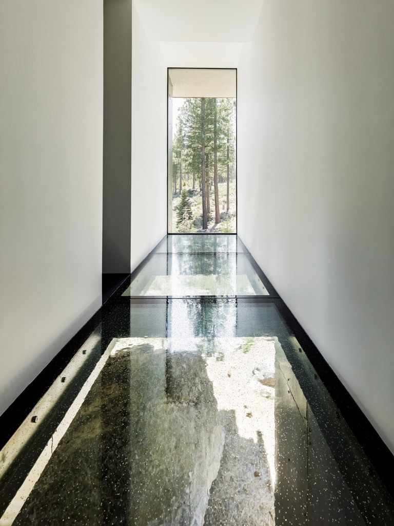 Glass floors here visually remove the boundaries and make the house more light filled, there's a large double height window