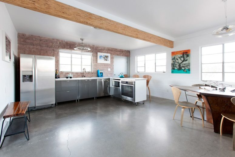 The kitchen and dining space comprise one space with wooden beams, an exposed brick wall and metal cabinets