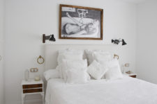 06 The master bedroom is spruced up with a cool artwork, vintage nightstands and a inviting bed with lots of pillows