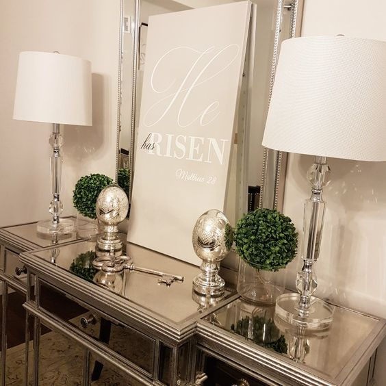 an elegant console table with mercury glass eggs and boxwood balls plus a poster