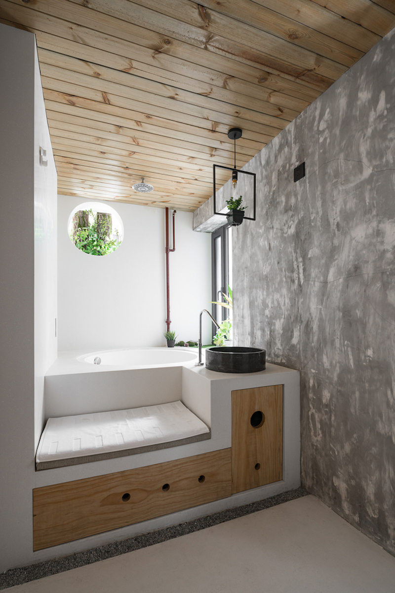 The bathroom is done with fresh greenery, industrial touches and a platform with storage, which incorporates a bathtub