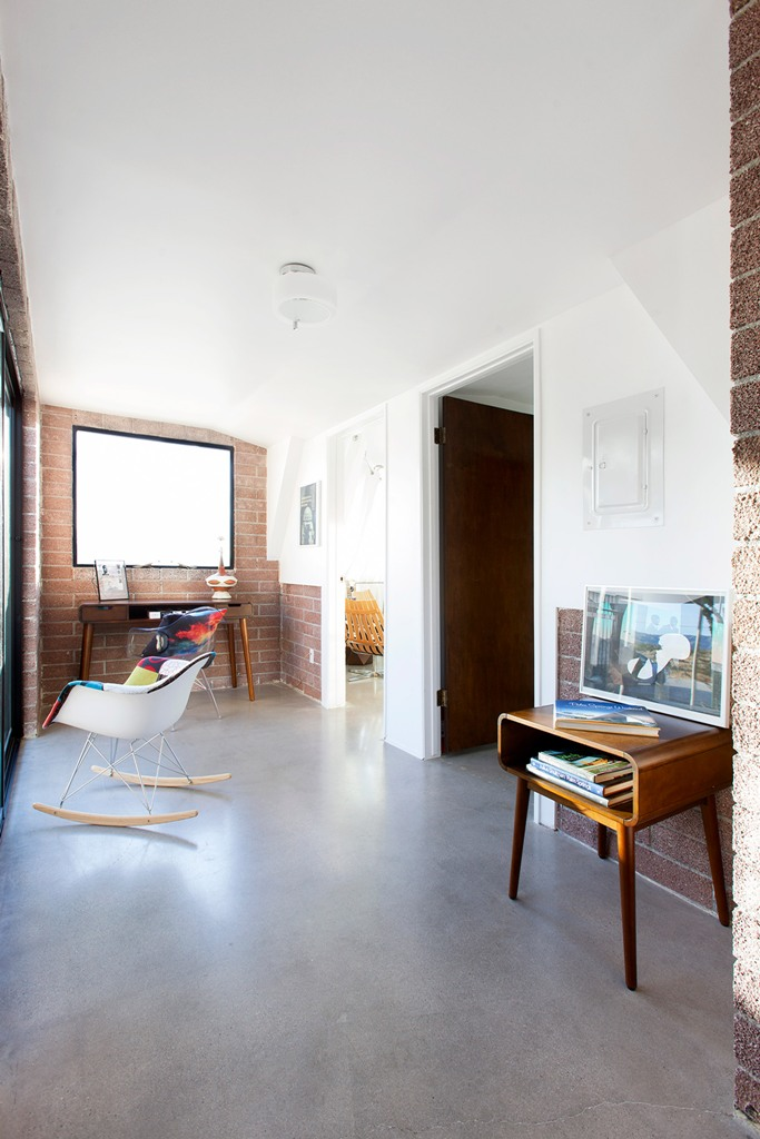 The home office is done with brick walls, mid-century modern furniture and is filled with natural light