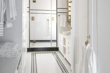 07 The master bathroom is done with black and white tiles and some brass touches for an elegant vintage feel