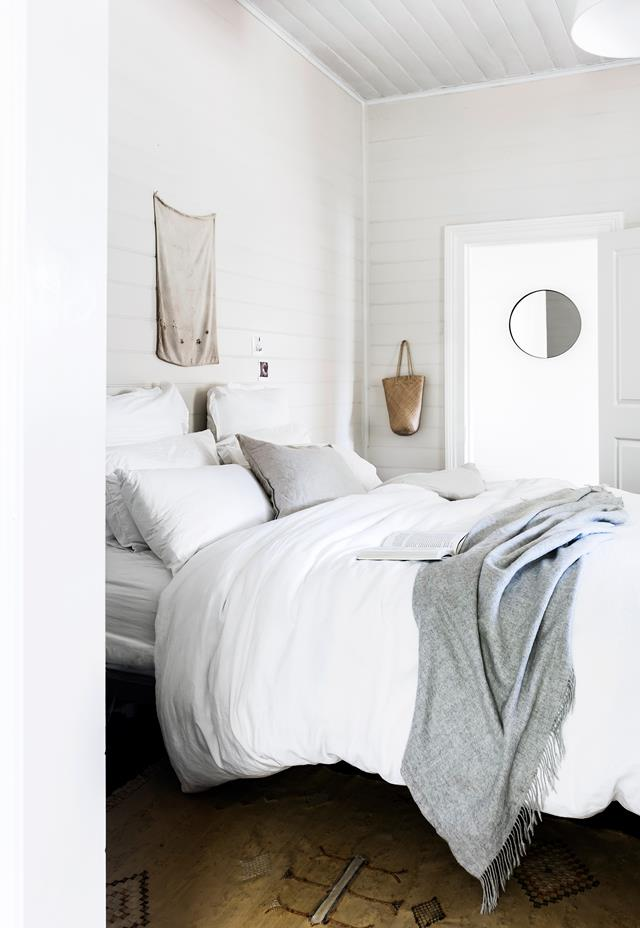 The master bedroom is a peaceful space with a large bed, a vintage rug and some accessories here and there