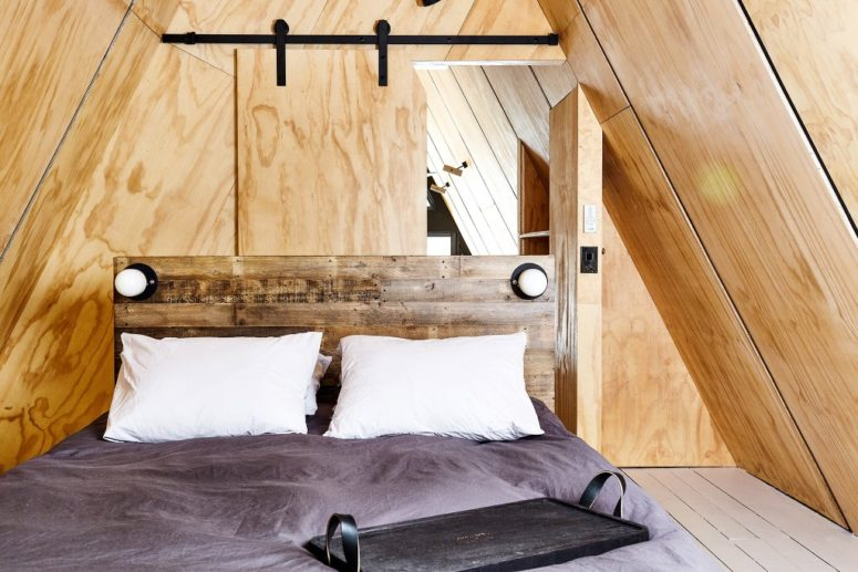The master bedroom is clad with plywood, there's a barn door and a reclaimed wood bed, there's nothing unnecessary