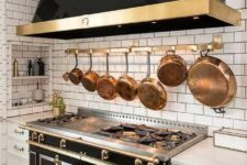 07 a large brass holder with a whole selection of vintage brass pots and frying pans
