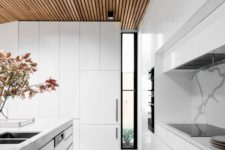 07 a sleek minimalist white space is accented with a wood slab ceiling and a large skylight for a natural feel