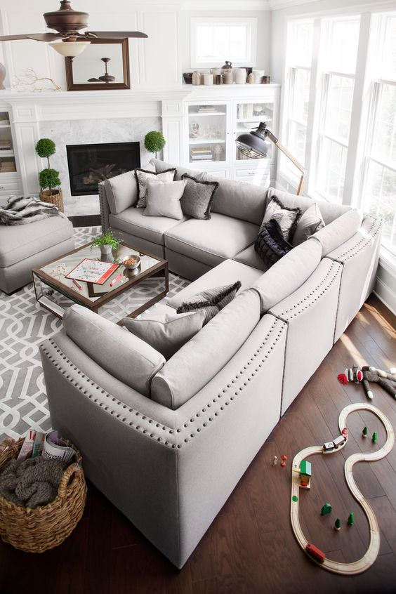 a stylish dove grey L-shaped sectional sofa with a matching ottoman as a basic piece for a living room