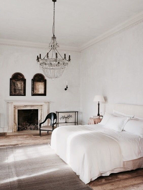 a vintage bedroom with a large crystal chandelier and fireplace and mid-century modern furniture