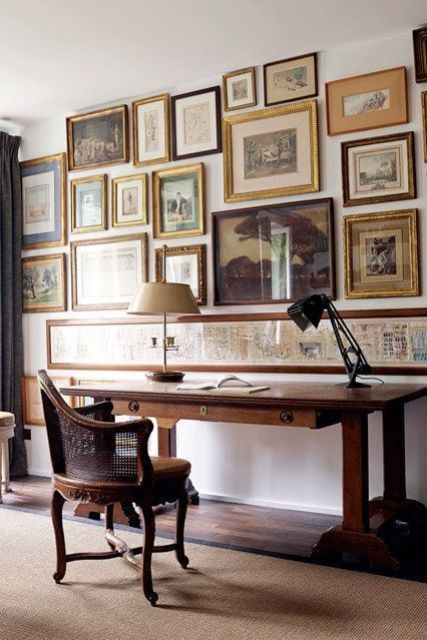 a vintage home office with a gallery wall that takes the whole wall, mismatched frames create a catchy look