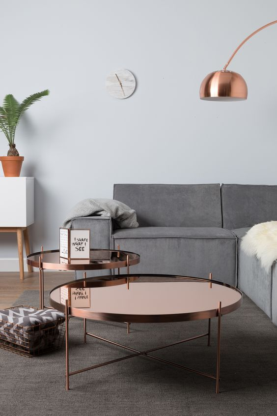 matching polished copper tables and a floor lamp add chic and brightness to the space