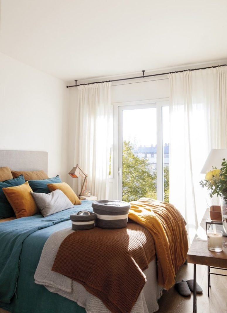 The master bedroom is decorated in contrasting and vivacious colors, there are layered textiles and cozy decor