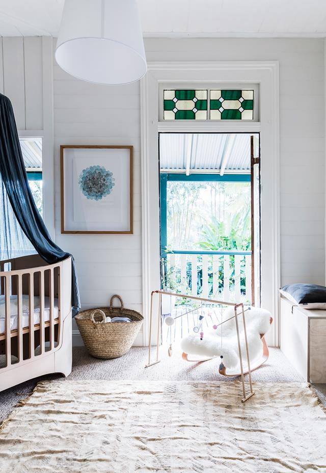 The nursery shows off a stunning modern crib with a dark canopy, some matching navy touches and cozy accessories