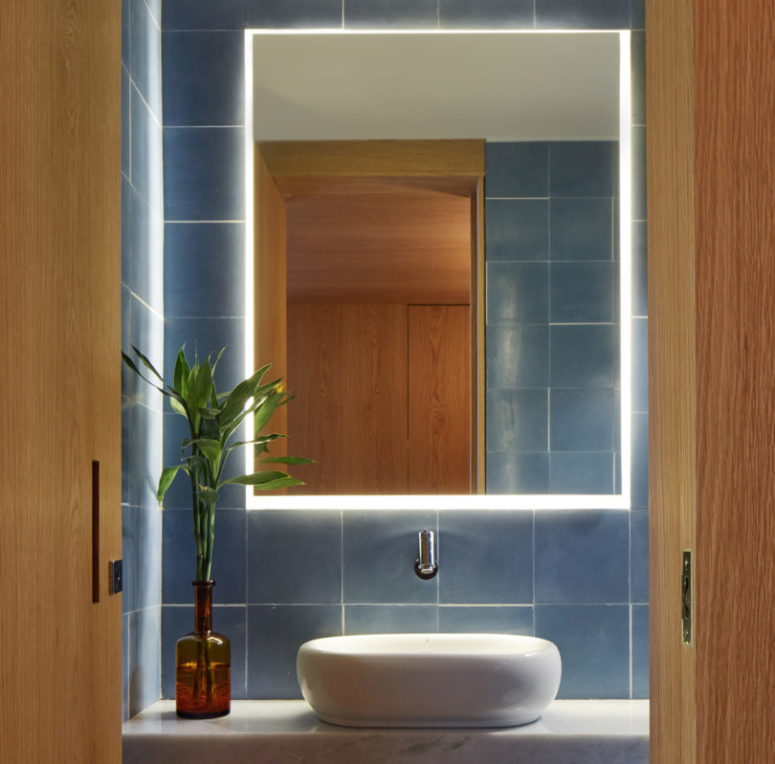 The powder room is done with blue tiles, a marble countertop and a sculptural sink and a lit up mirror